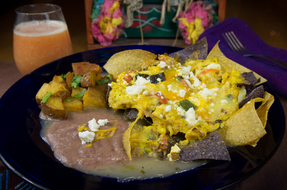 Migas, green sauce with glass of orange juice