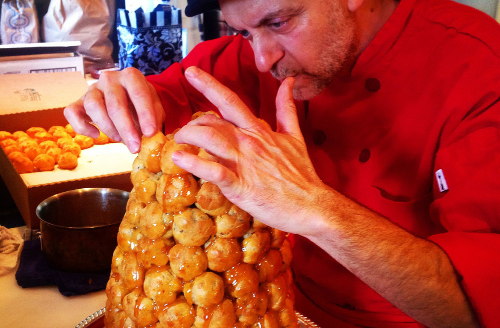 Croquembouche . A French dessert made of choux pastry, formed into a tower, and bound with caramel.