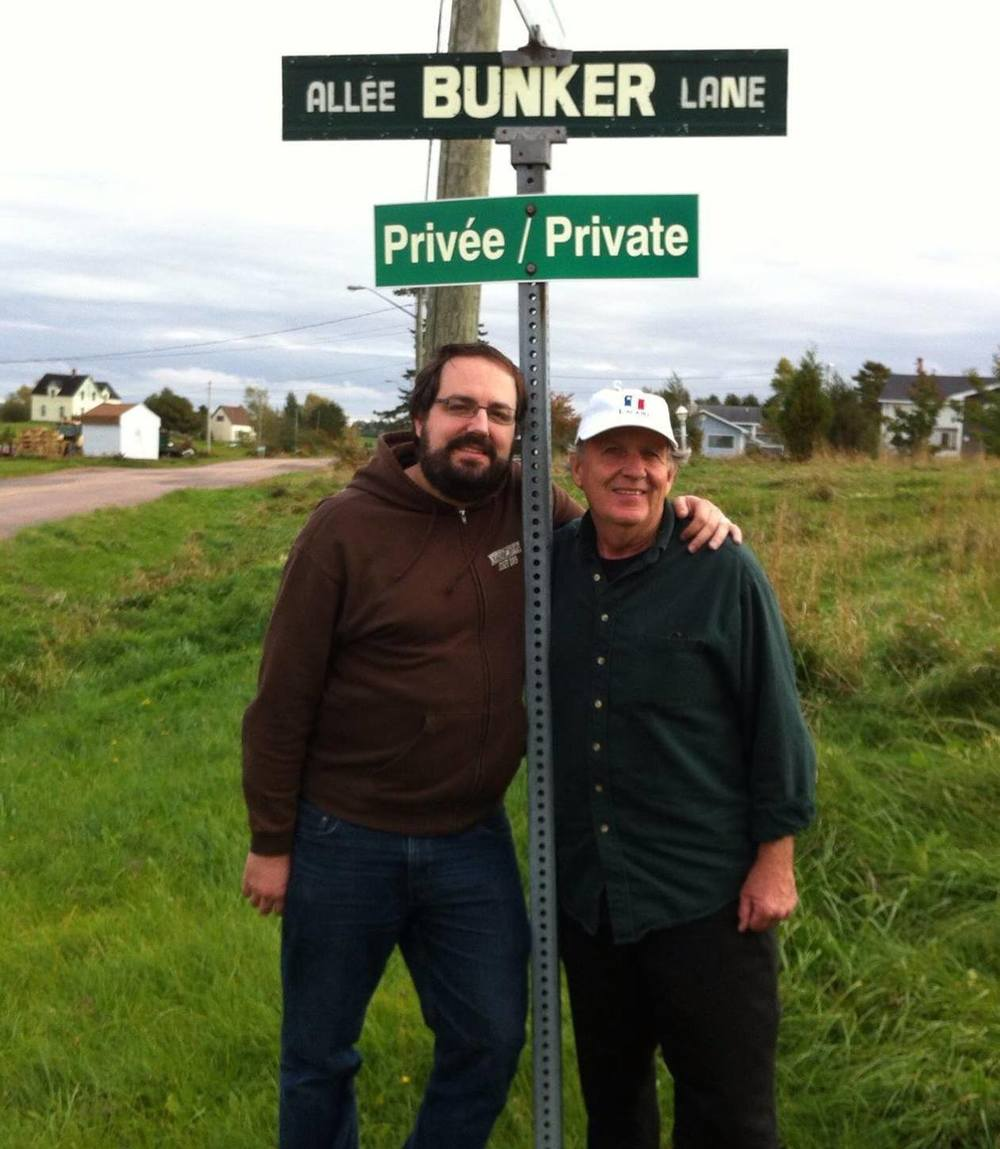 "Léger père et fils at the crossroads of Bunker Lane, named in honor of Louis' maternal great grandfather: Joe Bunker. His real name was Joseph Leblanc but since he had worked in a bank for awhile, folks called him ""Joe Bunker"" or Joe le banquier. Louis is ""le fils à Colombe, la fille à Ben à Joe"".     Léger père et fils au croisement de l'allée Bunker, nommée un honneur du arrière grand-père maternel: Joe Bunker. Son vrai nom était Joseph Leblanc mais parce qu'il avait travaillé dans un banque, les gens l'appelait Joe Bunker ou Joe le Banquier. Louis est ""le fils à Colombe, la fille à Ben à Joe""."