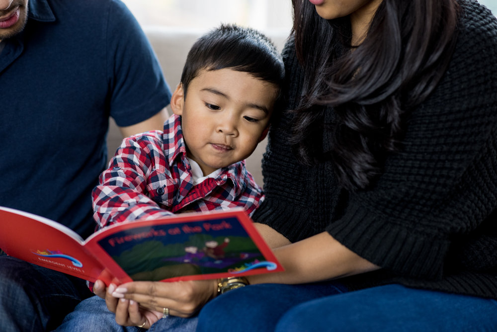 Child reading with parents