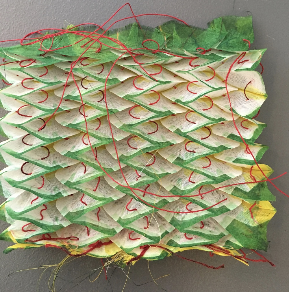 stitched shibori. Red thread on polyester with green and yellow dye by Elisa Ligon, one of our instructors