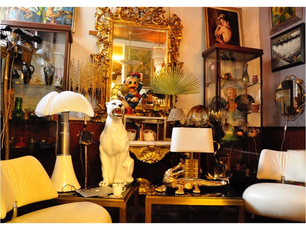 Twee wit lederen Leolux fauteuils. De spiegel dateert uit 1840. De lamp links is een Pipistrello van Gae Aulanti.