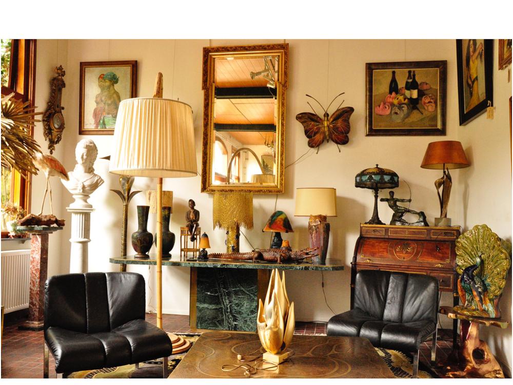 Zwart leren Deense stoelen, ontwerper onbekend. De bronzen sculptuur op de tafel is van Maison Charles. De spiegel dateert uit 1860. De bamboe booglamp komt uit de '70 jaren. Linker schilderij is van Fried Pal.