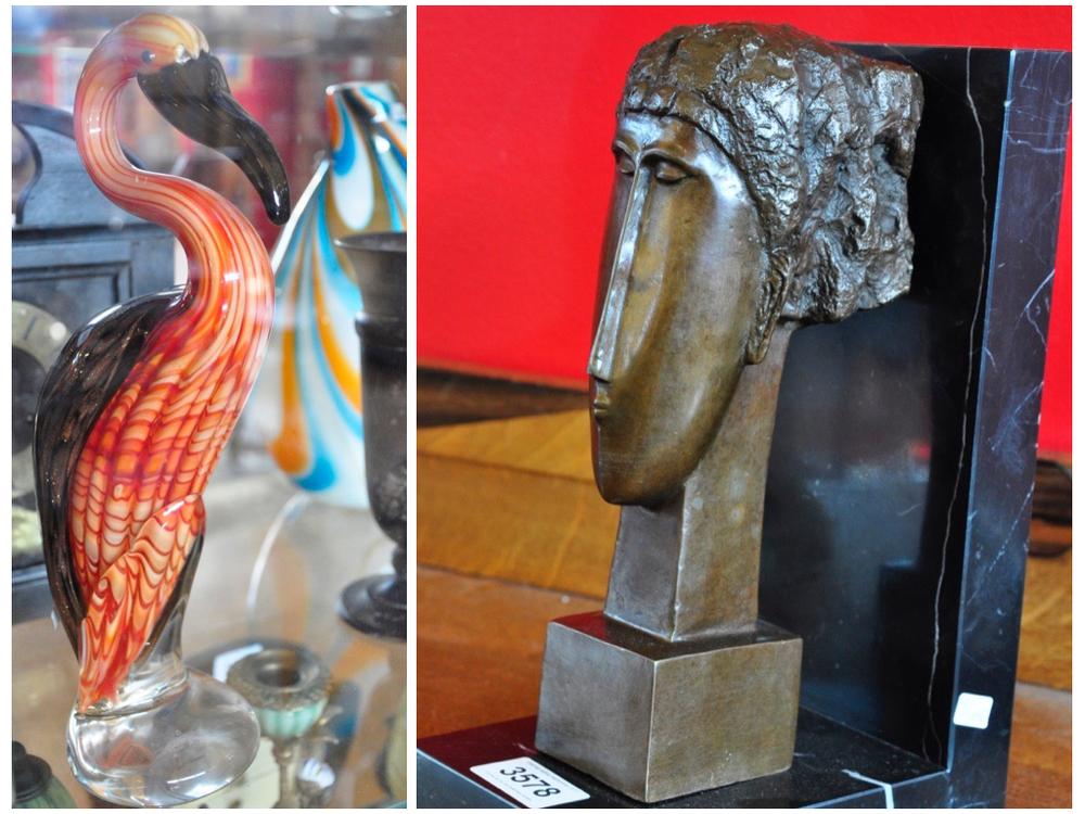 Set van 2 kraanvogels van dikwandig, gekleurd glas, H30 cm.Richtprijs € 60,- —€ 90,-. Marmeren boekensteun met bronzen sculptuur van gezicht naar Amedeo Modigliani, H26 cm.Richtprijs € 100,- —€ 150,-.