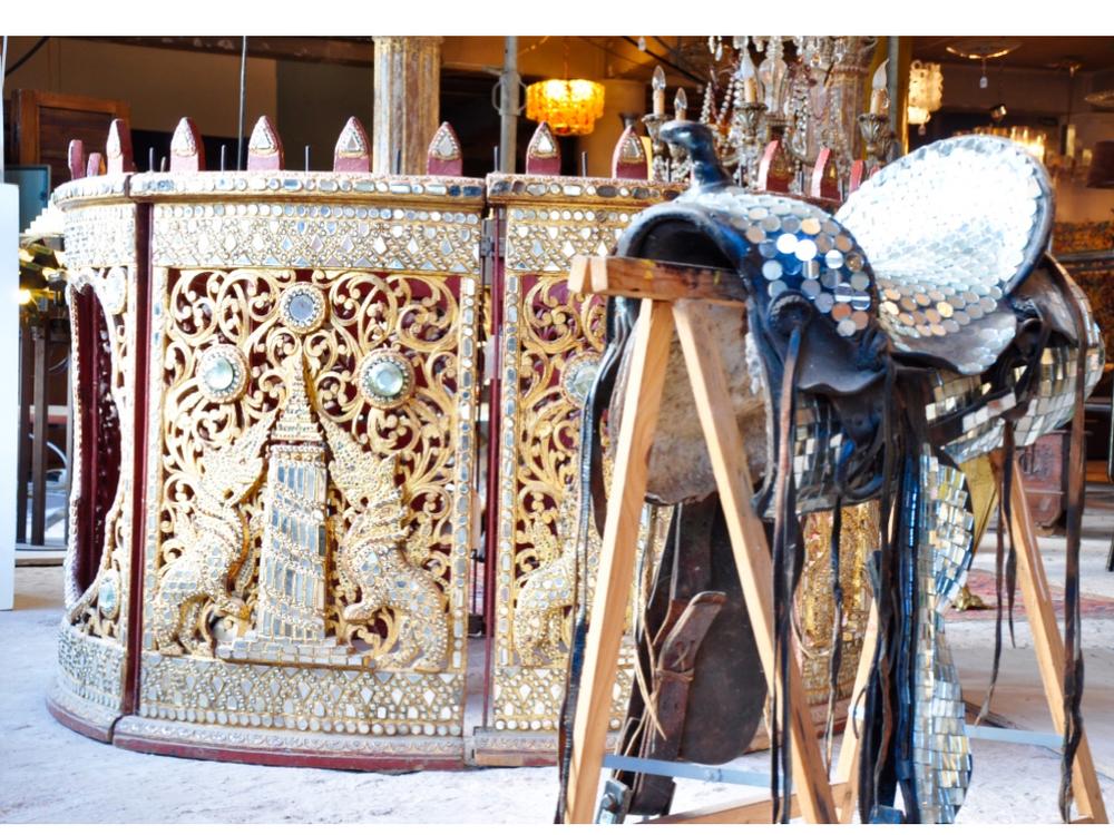 Het achterliggend ronde kunstwerk is een muziekinstrument uit Thailand. Aan de binnenkant hangen gongs. Het zilveren zadel op de voorgrond is een kunstwerk van George Heidweiller.