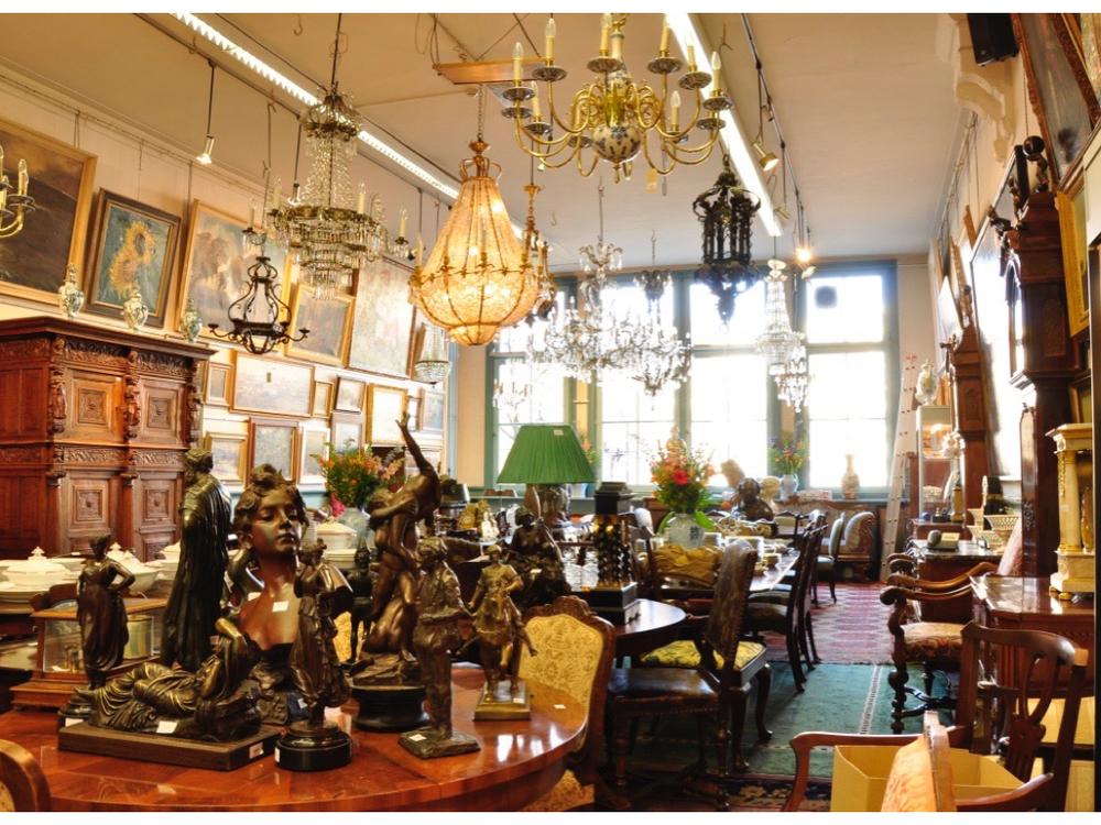 Zaal op de 1e verdieping met sculpturen, schilderijen, servies, antiek meubilair, lampen en uitzicht over de Keizersgracht.