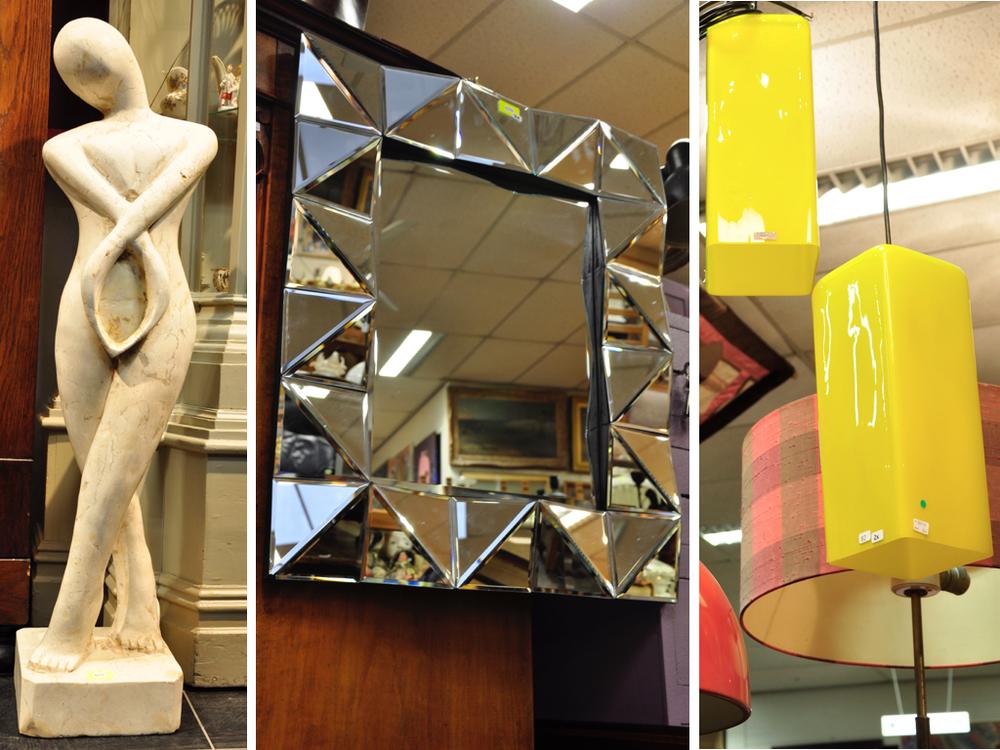 Natuurstenen beeld: staande vrouw, 103 cm. Richtprijs €80,-—€100,-.Spiegel met gefacetteerde rand en witte metalen opklapstoel (deze laatste niet op de foto).Richtprijs €30,-—€50,-.  Twee geel glazen hanglampen, uitvoering Vistosi, Murano, Italië, 32 x 12,5 x 12,5 cm.  Richtprijs:  € 150-200 .