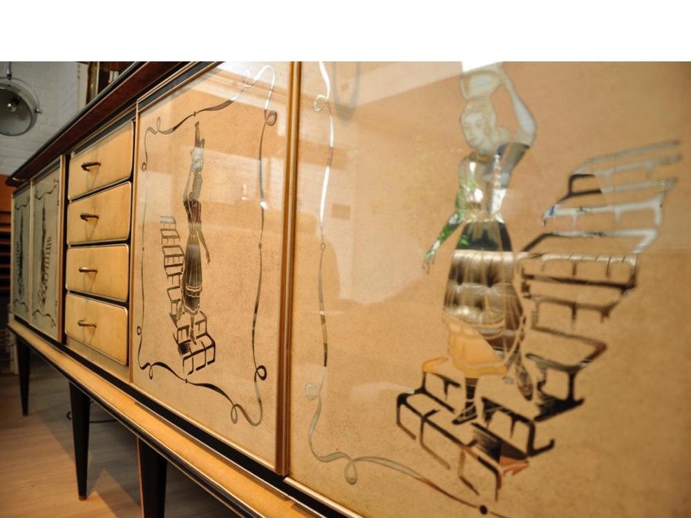 Groot dressoir met afneembare spiegels,van Umberto Mascagni uit Bologna. In het begin van de jaren '50 gemaakt voor Harrods in Londen. Met glazen topblad,sierranden van geanodiseerd aluminium, vinyl en 'kunst lizzard-skin' bekleding ook om de poten.Mascagni maakte gebruik van allemaal nieuwe technieken en materialen voor die tijd en was daarmee ook enigszins provocerend. De deurfronten zijn uitgevoerd in speciale spiegelende prints met glasinzet. Prijs op aanvraag.