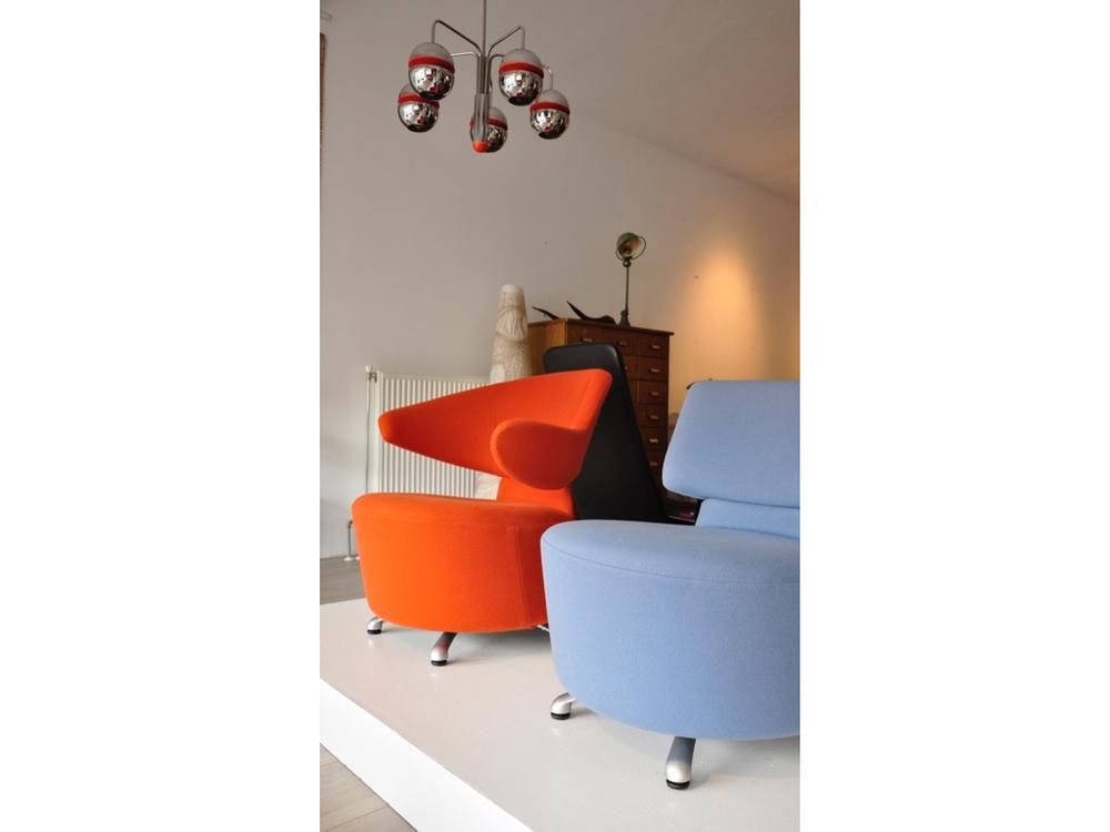 Oranje draaibaar design fauteuil van Cassina Canta Chair ontwerp van de Japanse Toshiyuki Kita.Licht blauw,draaibaar design fauteuil van Cassina Aki Chair ontwerp van de Japanse Toshiyuki Kita. € 875,-.Belgische Kroonluchter van Chroom met oranje accenten uit de jaren '60 bestaande uit 5 lichtpunten, € 725,-.