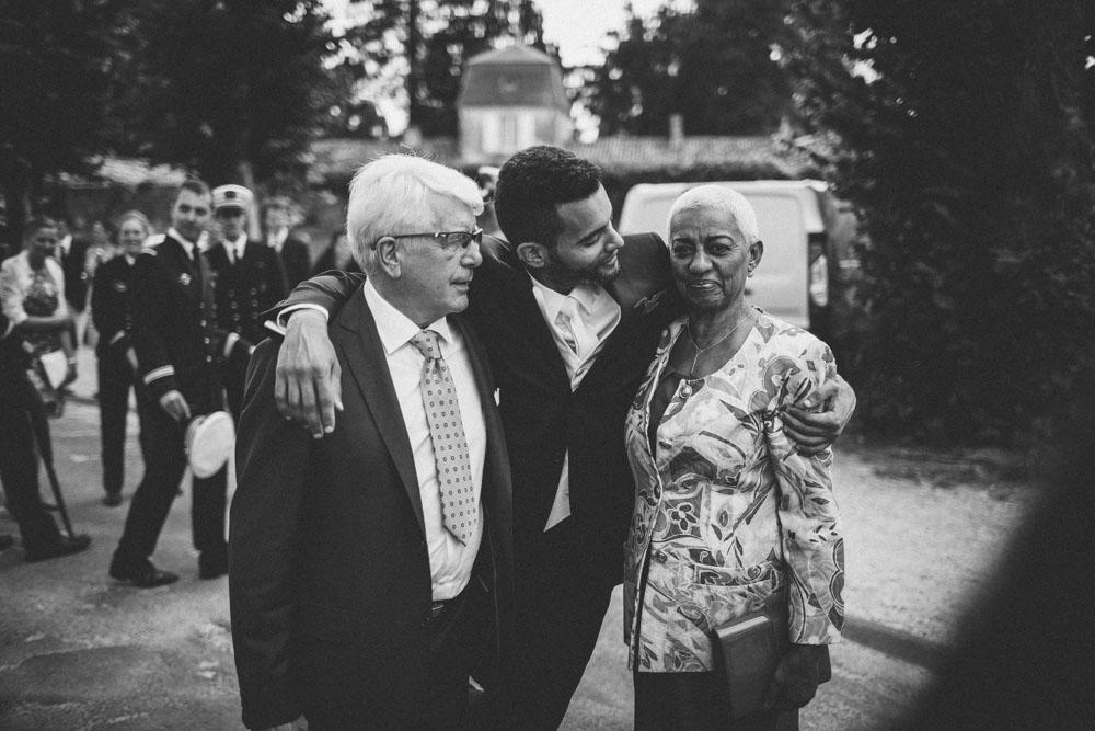 Photographie en noir et blanc d'un marié avec ses parents. D'origine guadeloupéenne, sa mère est très émue.
