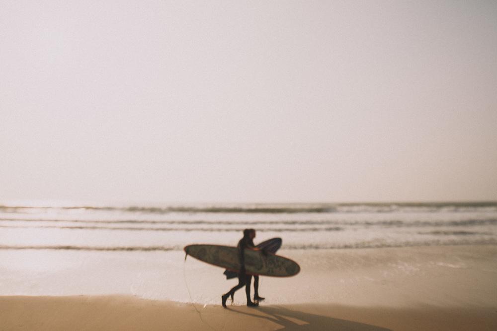 Deux surfeurs de Biscarrosse marchent sur la plage.