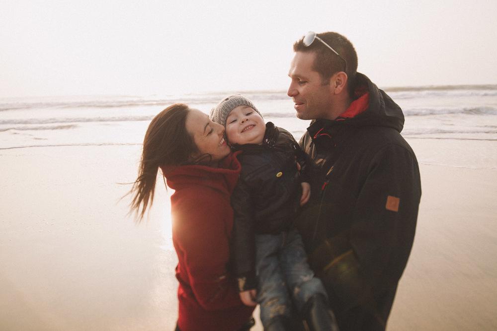 Cette mère embrasse son fils sous le regard du père, ils sont heureux.
