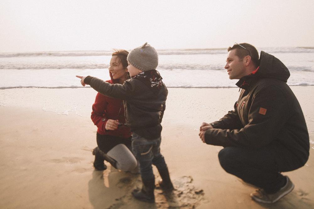 Le petit Thom montre quelque chose au loin à son père et sa mère.