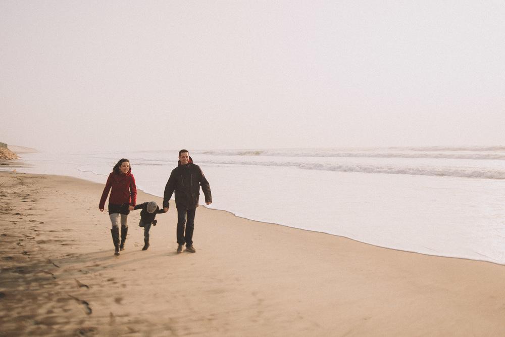 La petite arrive en marchant sur la plage pour la séance photo.