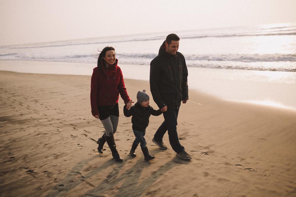 Petite famille se baladant sur le sable.