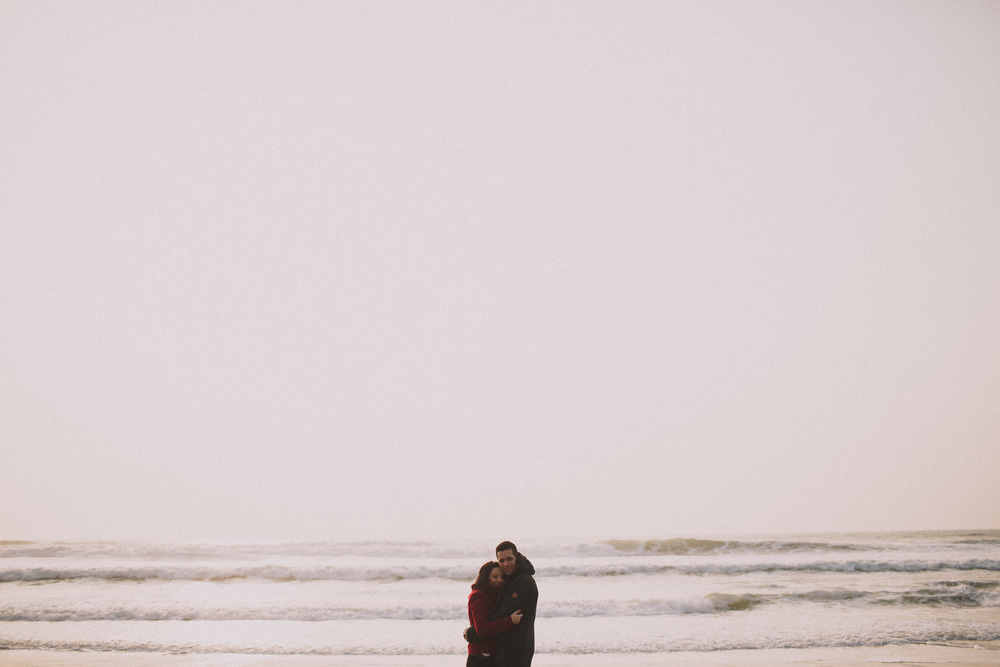 Une vue éloignée du couple enlacé, devant les vagues.
