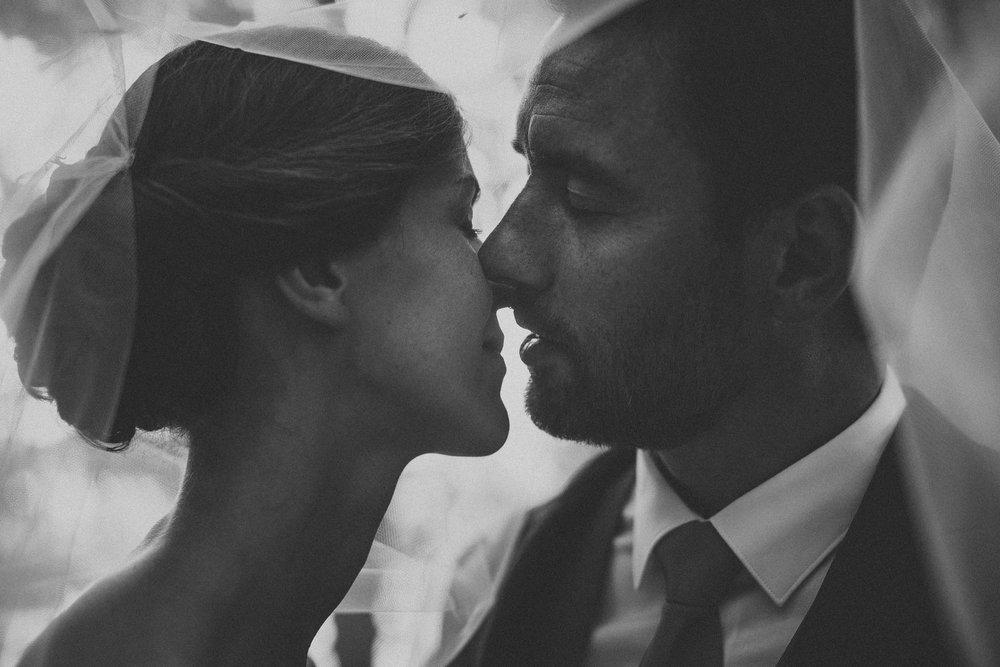 Un couple de mariés s'embrasse avec amour, on peut lire leur bonheur sur cette photographie.