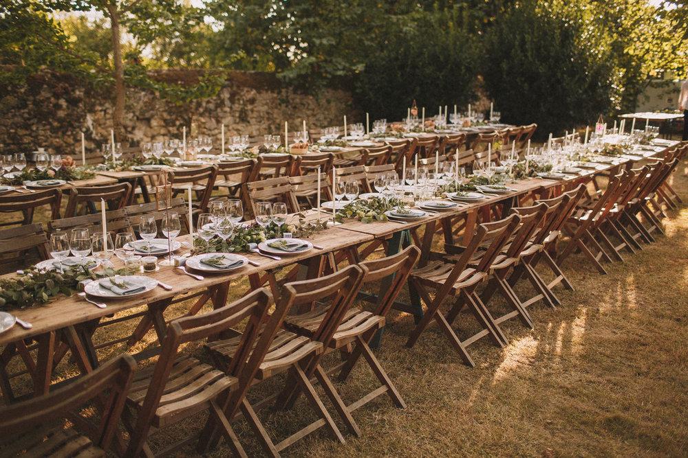 Photographe mariage Bordeaux. Magnifique table pour ce dîner repas de mariage en extérieur. Bois, guirlande, fleurs et plantes vertes. Jérémy Boyer.