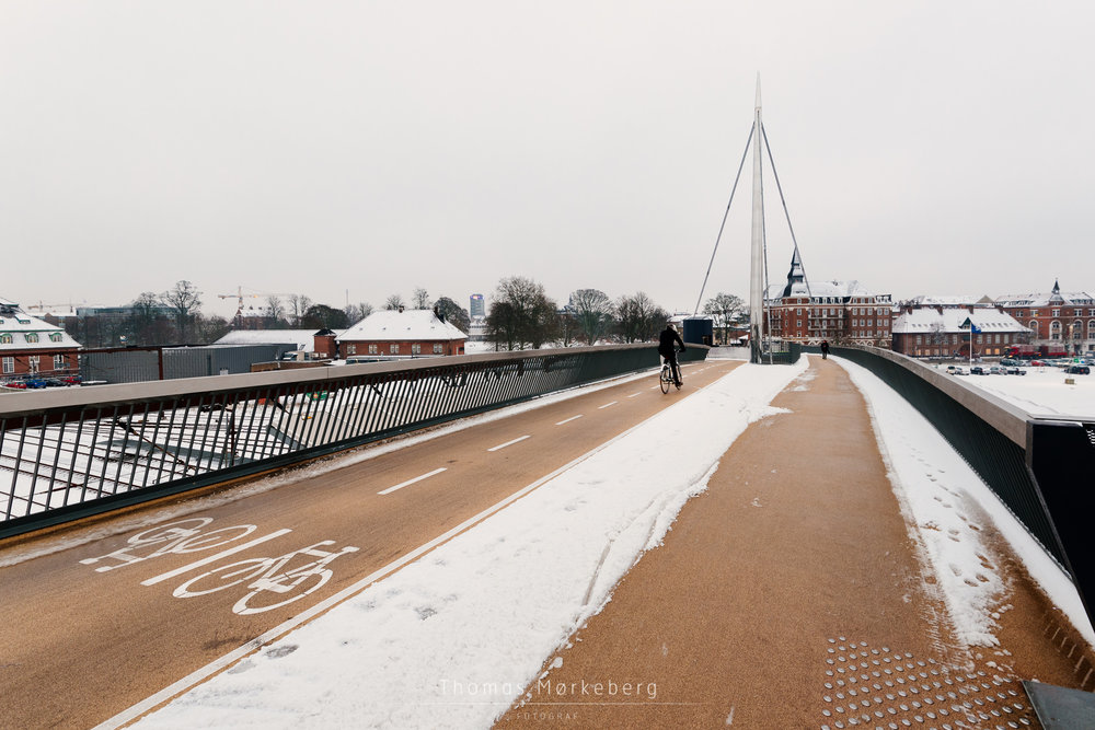 Cyclist in the snow on Byens bro (bridge) in Odense, Denmark