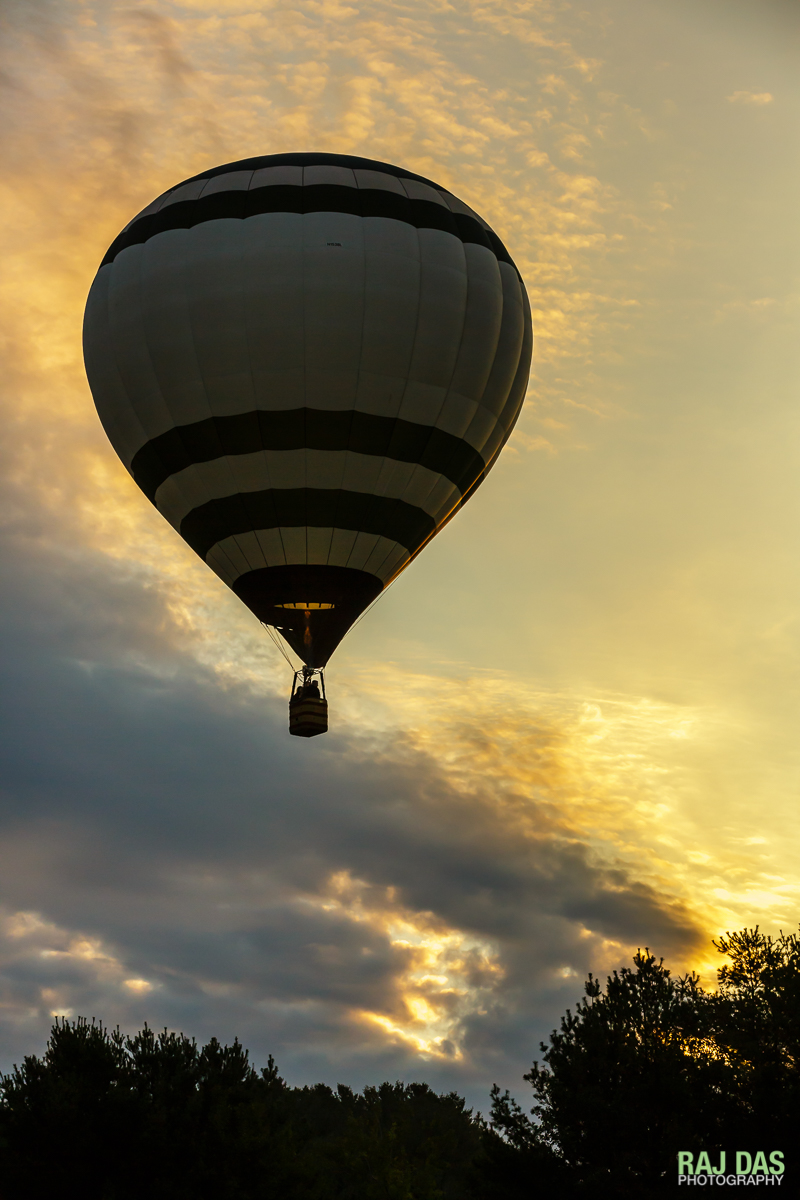 The first balloon ascends as the early rays of the morning sun kiss the sides