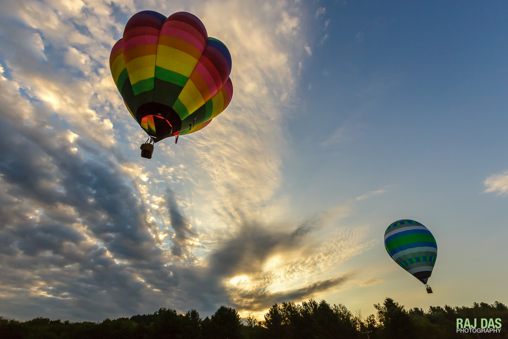Balloons sail away as a dramatic sunrise fills the skies