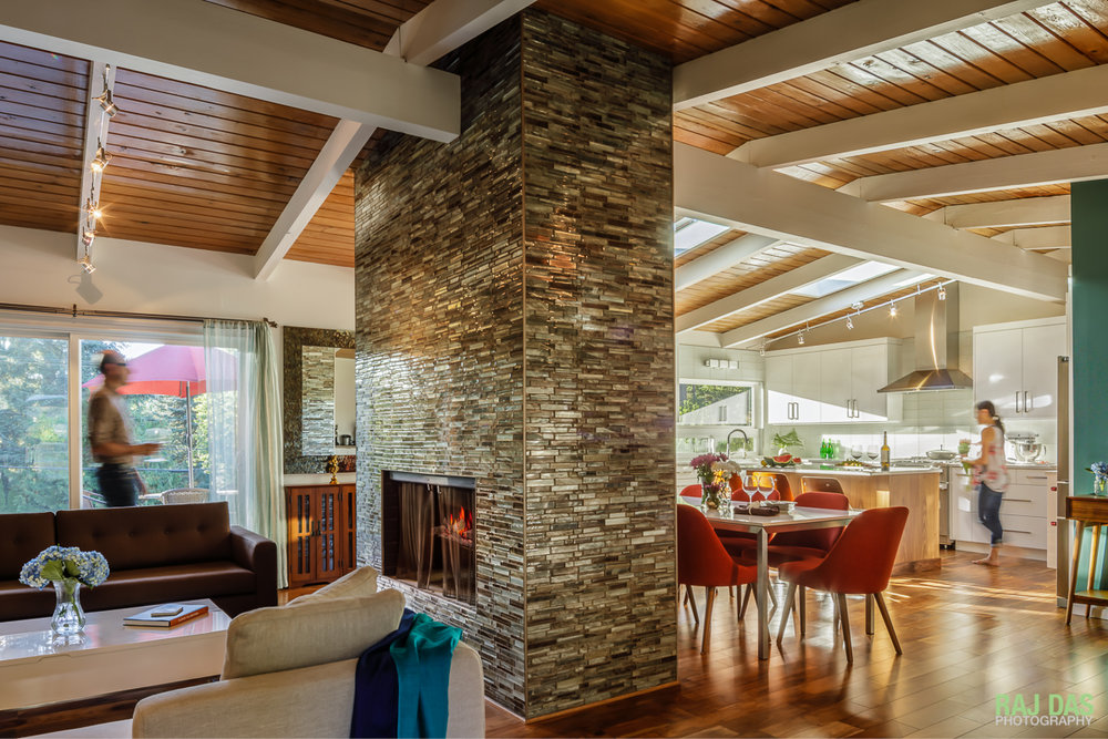 A view of the living space, dining and kitchen area and the outdoor front patio. The fireplace and center column separates the living from the dining space while preserving the flow and openness.