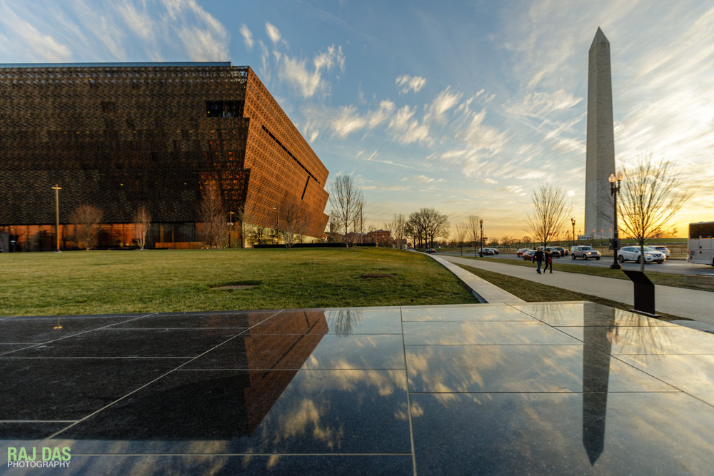The Museum and the Washington Monument reflected on the black granite retaining wall