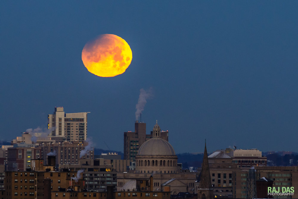 A close shot of the super blue blood moon with the dome of the First Church of Christ, Scientist in Boston visible in the center of the frame.