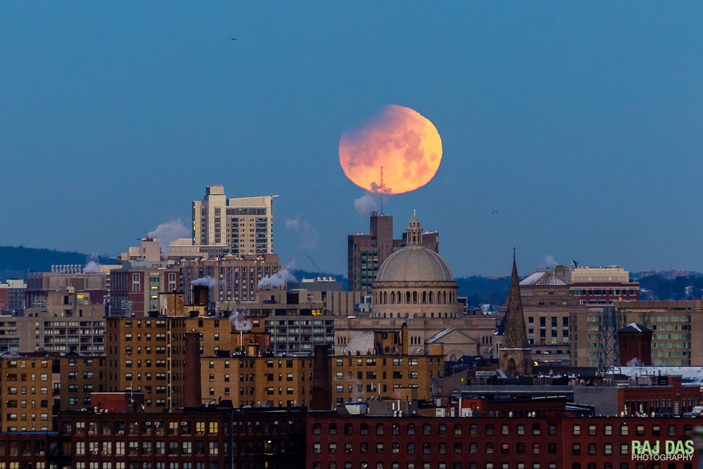 A close shot of the setting super blue blood moon with the Boston skyline and dome of the First Church of Christ, Scientist visible.