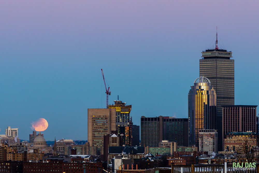 A super blue blood moon sets just as the sun rises in the opposite direction casting a warm glow over the Boston skyline.