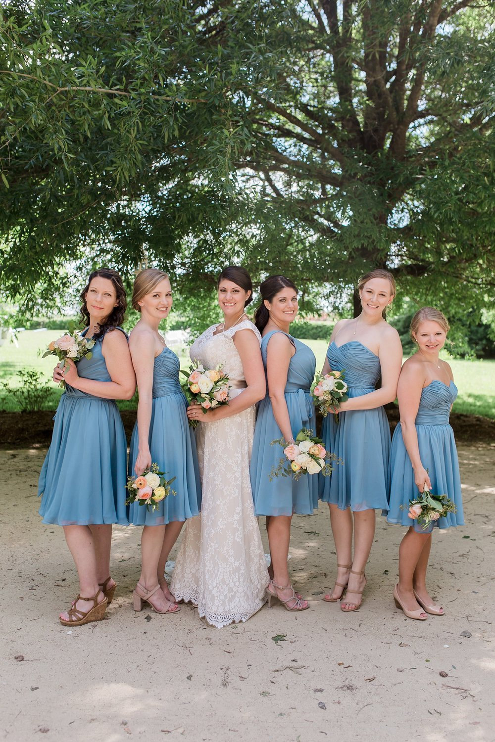 Classy blue bridesmaids with white and peach flowers