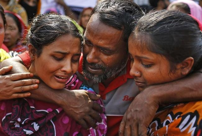 Relatives mourn their grandfather who was killed when a garment factory collapsed in bangladesh in 2013. over 1,000 people died that day. Photo Courtesy of India Times