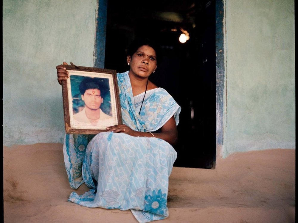 a woman holds a picture of her husband who committed suicide. he borrowed money to purchase cotton seeds and pesticides. the crops failed due to a lack of rain. Photo and story courtesy of   The gaurdian