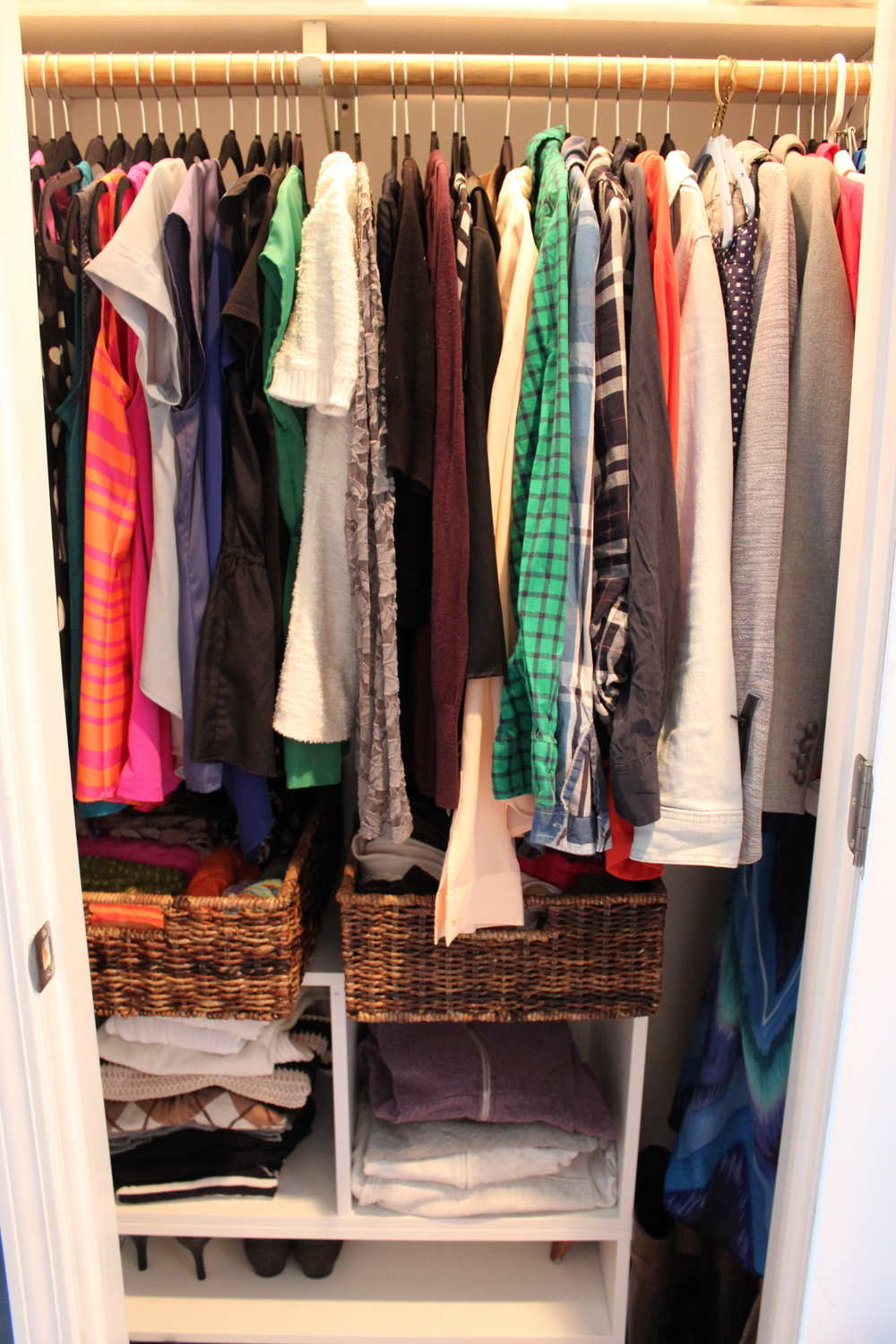 "The ""After"". We added storage on the bottom to use the space all the way up to the hanging clothes. Baskets help to keep scarves and smaller garments neat and tidy!"
