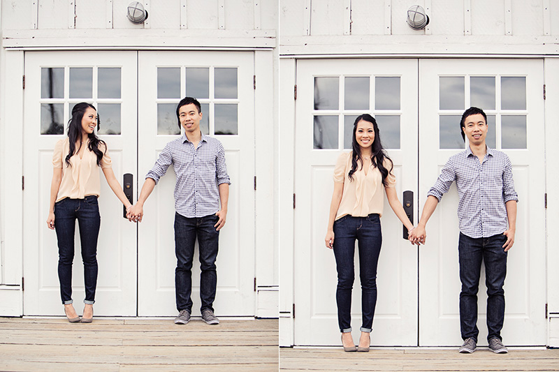 engaged couple holding hands in front of old white barn