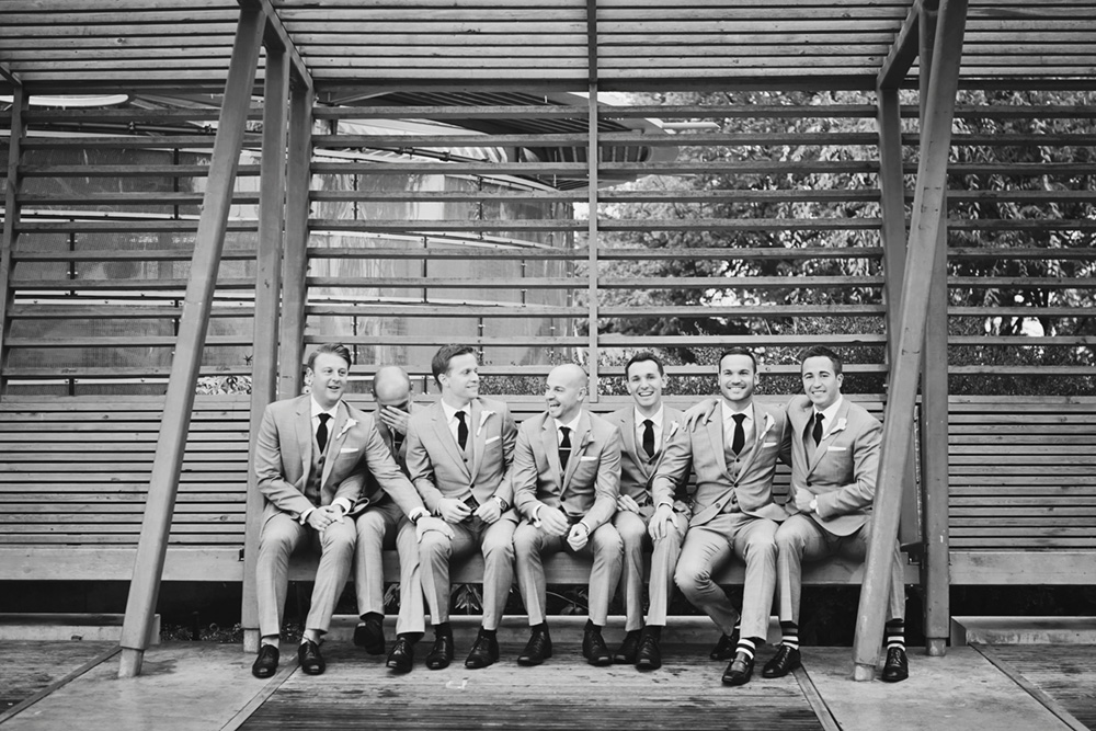 Groomsmen sitting on a bench sharing a laugh