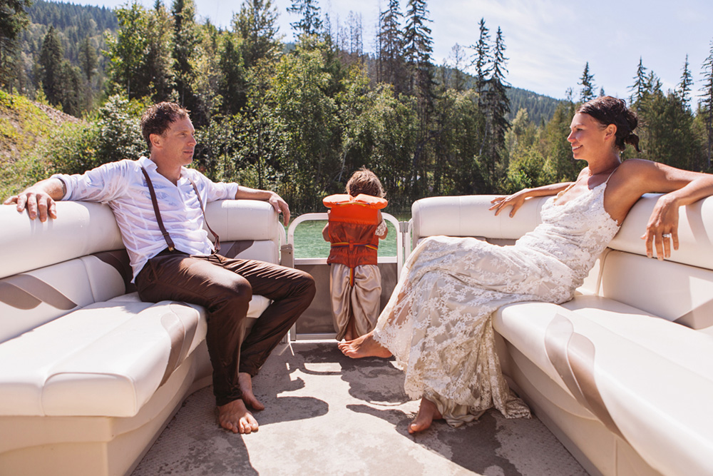 Vancouver Wedding Photography: Bride and groom sitting in a boat with their child after a swim