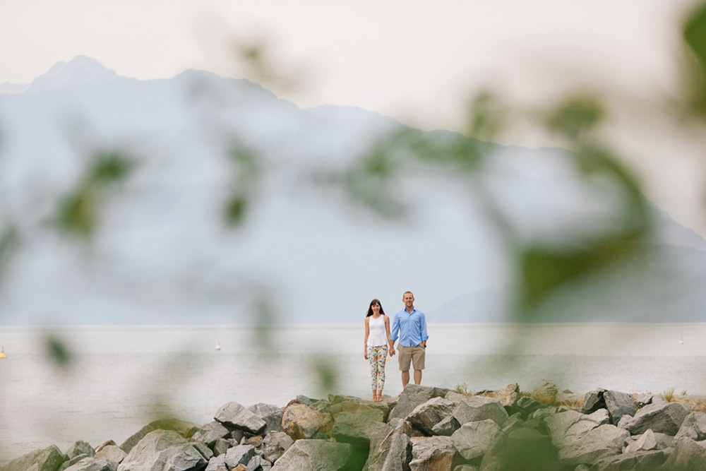 couple seen through blurry trees  by Vancouver photographer