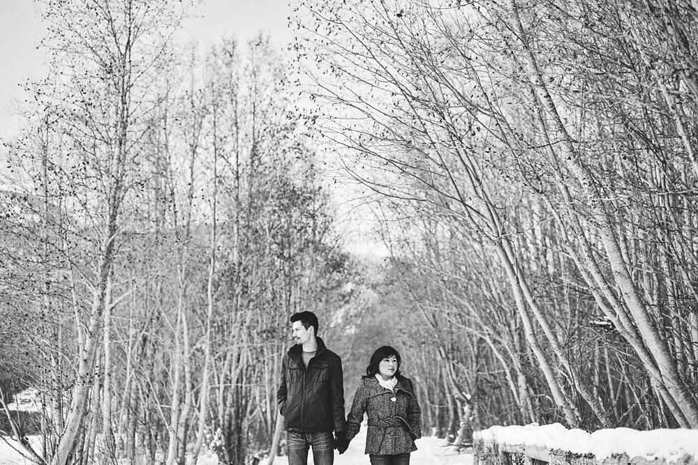 black and white image of couple in snowy forest