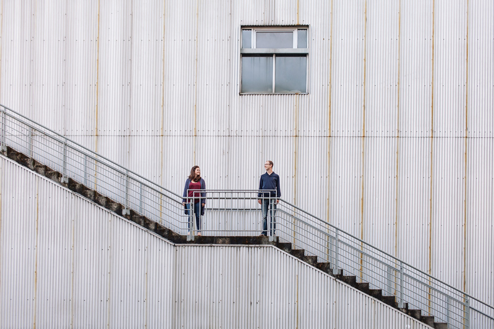 wide angle portrait of couple in front of metal building