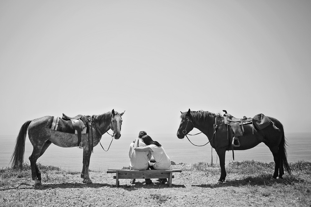 couple sitting between two horses