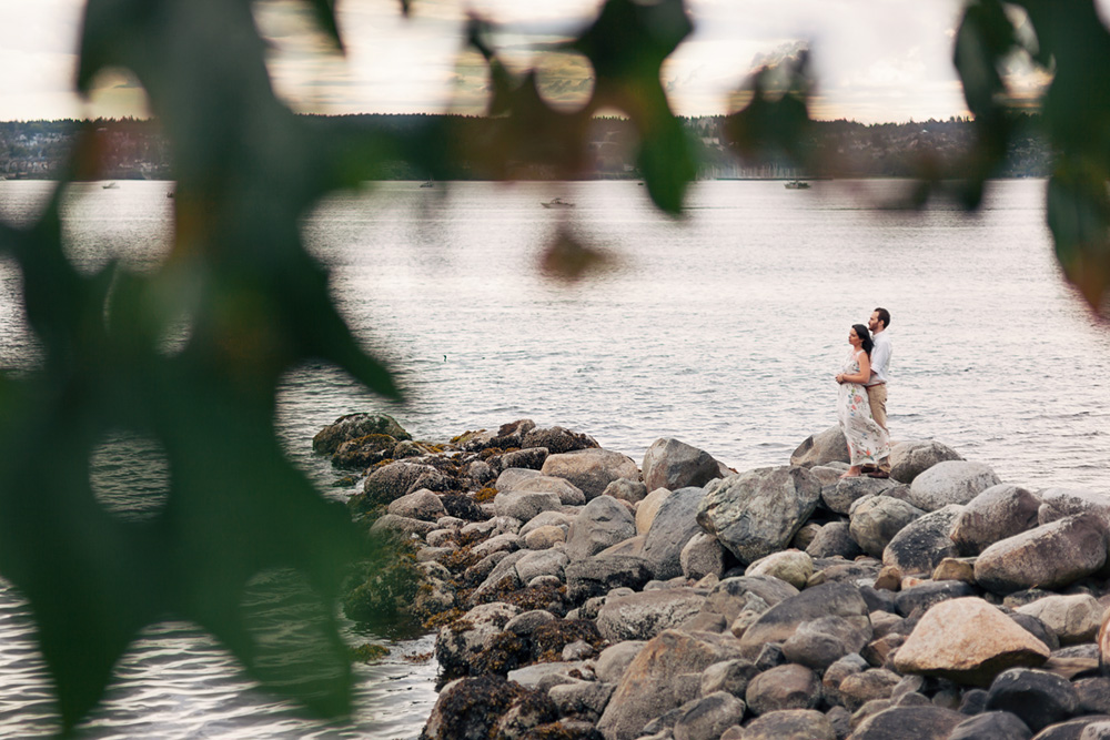 couple with arms around each other on beach by Vancouver photographer