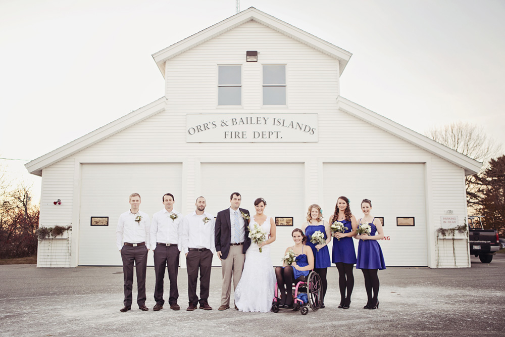 A wedding party in front of an old firehall
