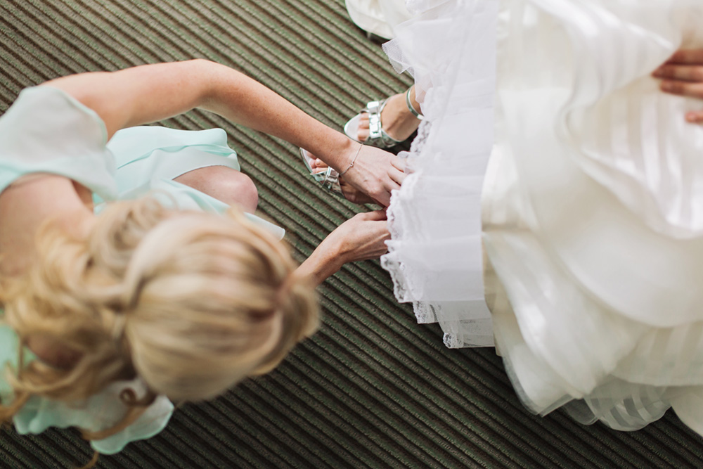 Bridesmaid helps with the shoes