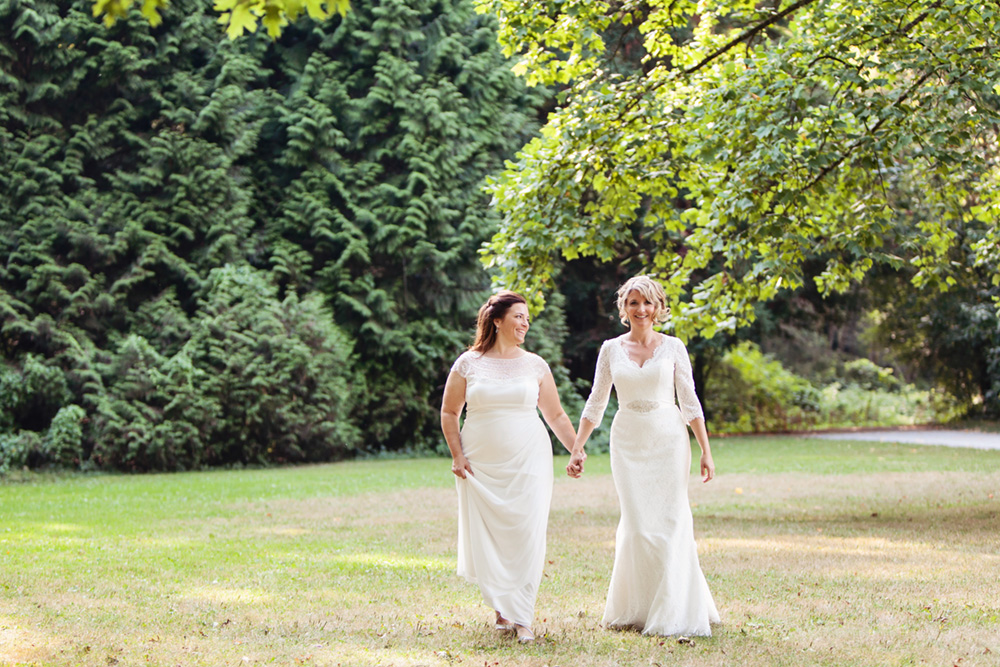 Two brides walking in a park