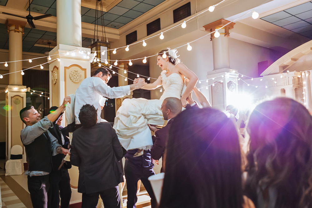 bride and groom being lifted in chairs
