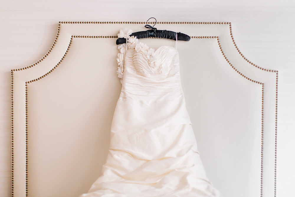 wedding dress hanging on a bed
