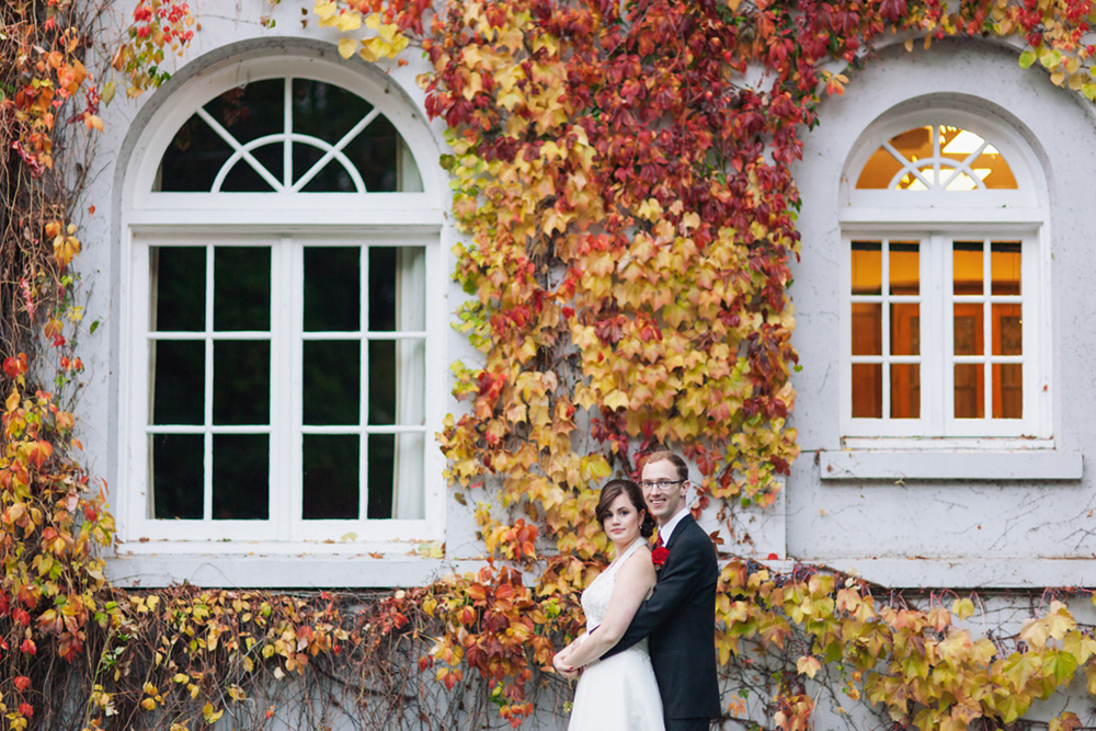 bride and groom in front of fall vines on building