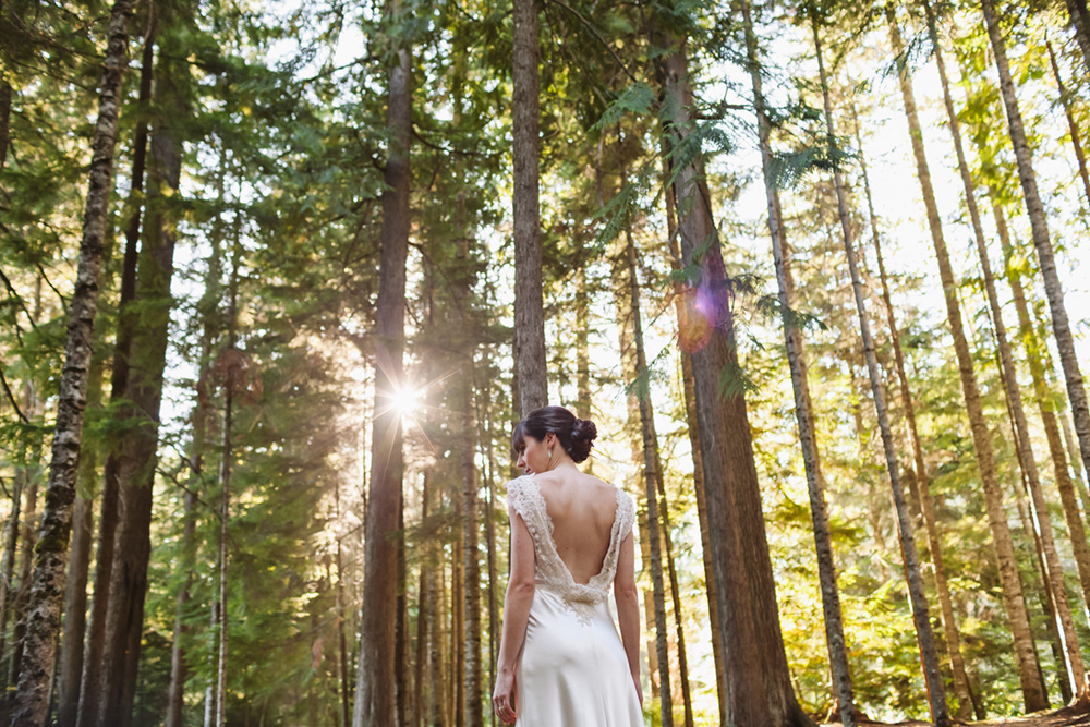 bridal portrait in forest with sun peeking through