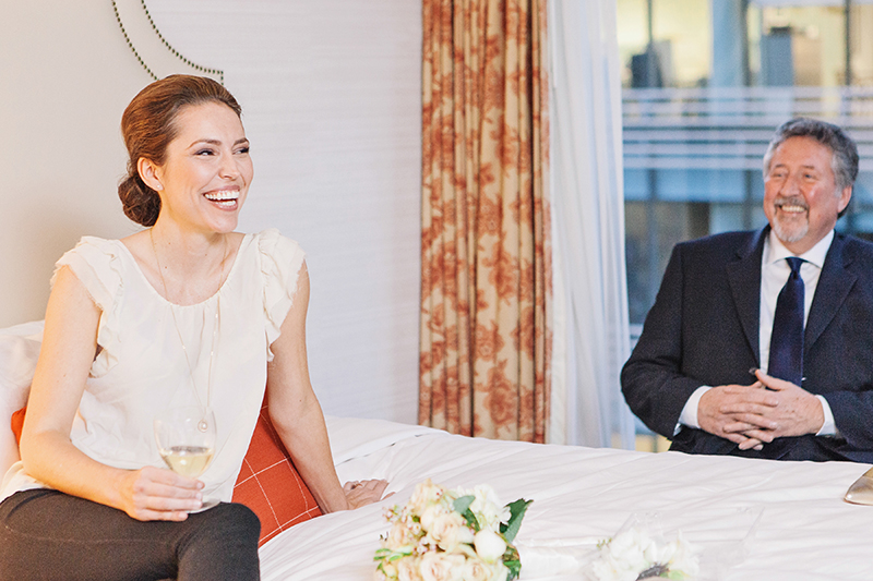 bride laughing while sitting on a bed